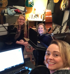 Karen, Susannah, and Gillian in the recording studio. surrounded by a wall of guitars, a bass, and laptops on music stands